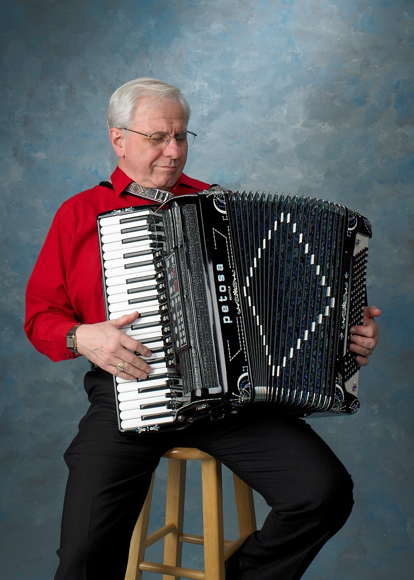 John Custie, a live musical entertainer, plays an accordion on a stool in Long Island, NY